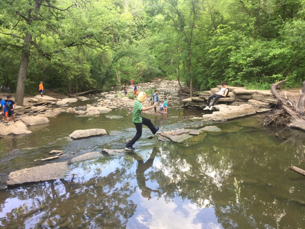 boy using rocks to cross creek above small falls